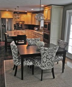 so pretty kitchen + dining room. Very much my style. Love the grey & white patterned chairs with dark table!