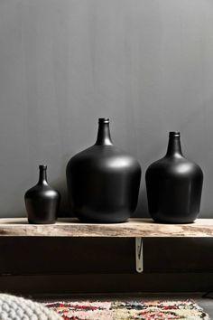 vaas karaf mat zwart glas op houten plank met antraciet muur