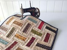 I love the simplicity of this little quilt! I made it with Civil War reproduction fabric scraps in reds, blues, greens, creams, browns, golds, and teals. The pattern I used is called Railfence. This little quilt measures about 14 3/4 square and would make a pretty little table