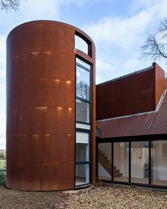 Chris Dyson Architects created a contemporary extension to a traditional cottage in the heart of the Cotswolds.| A circular tower echoes the former gas storage cylinder that once occupied its place. It houses a private study.