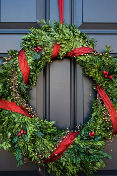 Boxwood wreath with berries and red ribbon. Elegant and festive Christmas wreath for your front door. -- If it's a dried wreath, you could even remove the decorations, and reuse the wreath for other times of the year.