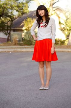 Bright skirt and a gray sweater.