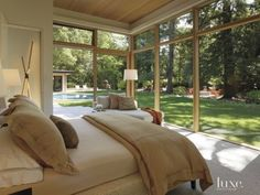 Modern Glassed-in Master Bedroom Room & Board's Holden chaise tucks into the glassed-in corner of the master bedroom, inviting views of the sylvan surroundings. Plantation's Anson bed is upholstered with fabric from the Windsor Smith for Kravet collections.