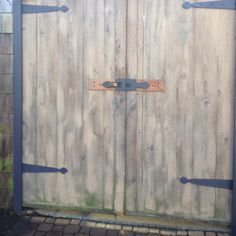 Shed door with cherry wood faux hinges cut n painted to look like wrought iron based on winery doors made by Steven Wells