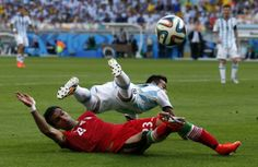 Iran's Mehrdad Pooladi, bottom, challenges Argentina's Ezequiel Lavezzi during the group F World Cup soccer match between Argentina and Iran at the Mineirao Stadium in Belo Horizonte, Brazil, Saturday, June 21, 2014.
