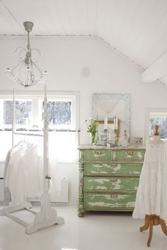 chippy green dresser in a white room