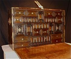 Late 16th Century Early 17th Century Walnut Bargueno.Constructed from solid walnut and decorated with gilded and pierced metal ornamentation behind which is red faded silk and fitted with a lock, gothic tower hasp and key. The fitted interior with six rows of highly decorative drawers and cupboards with ivory/bone turned and gilded pillars.  Height: 28.50 inches Width: 44.50 inches Depth: 17.50 inches (closed)