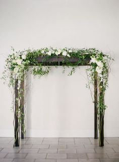 dark wood arbor decorated with white flowers and greenery