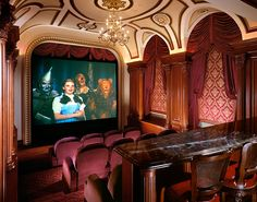 This home theater room reminds one of a bygone era, with its magnificent ceiling and decorative applied moldings.