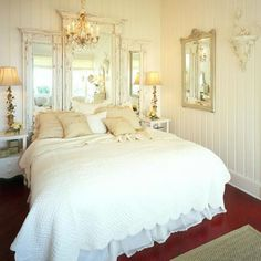 Three vintage mirrors make for the most romantic and decorative headboard in this shabby chic room.