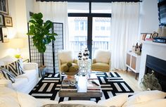 Amelia Canham Eaton's Chicago Apartment // living room // black and white // black and white rug // white couches // coffee table // balcony // chevron ikat pillows // Photography by Jennifer Kathryn Photography