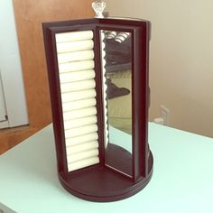 """Rotating Jewelry Stand Only used for a month or so. Includes a mirror, 3 shelves, a ring holder and 6 hooks for necklaces/bracelets. A dark brown almost black color. Very sturdy. About 13.5"""" tall. Jewelry"""