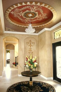 Foyer ceiling, design on overscale medallion. Also, consider frame out motiff around existing plaque for better scale at foyer hall niche