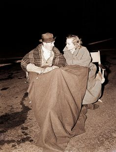 Clark Gable and Carole Lombard chat in a cold parking lot in Los Angeles during night shooting for Too Hot to Handle, starring Gable. July 9, 1938.