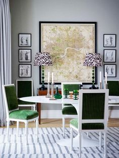 Dining room  with a white marble table, green upholstered chairs, and a large framed map