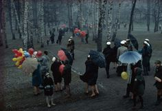 People strolling through a park in Finland during a wet May snowstorm, 1968.  PHOTOGRAPH BY GEORGE F. MOBLEY
