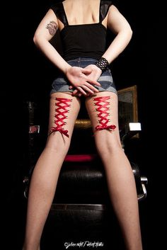 Girl with Red ribbon corset piercing on back of her legs