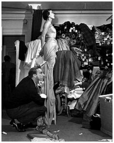Jacques Fath contemplates the drape of a fabric on a model, 1952.