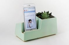This multi-functional phone dock accommodates a wide variety of smartphones including the iPhone, Galaxy Note, Motorola Droid, and many more. It features a large compartment for small plants or desk accessories. All we have to do now is pick our favorite color!