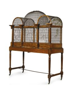 An early Victorian mahogany domed birdcage circa 1850. The cage with central dome flanked by Ionic columns supporting arches, above sliding feeding trays; on a stand with turned legs joined by iron stretcher, all on brass castors. #Victorian #Birdcage