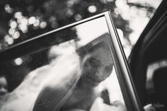 Bride getting in the wedding car. Love this raindrops! Black & white. Wedding Photography by Jere Satamo.