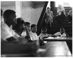 Teenaged Freedom School students take part in class discussion sitting at a table in the basement room of probably St. Paul United Methodist Church. George Ann Adams is the only female student on the left. More students sit at a table in the background, at the foot of a flight of stairs, on which are sitting three Caucasian male adults, probably volunteers.
