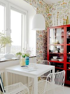 Awesome wallpaper in this kitchen.  Scandinavian white apt w/ pops of color.