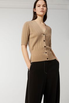 Knitted with a stripe structure, this short-sleeve cardigan is made of soft organic merino wool. The yarn used is a unique ARKET development. The garment s