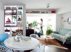 O apartamento tem apenas 70 m², mas a sala é ampla, com poucos e pequenos móveis. A prateleira no alto oferece mais espaço para guardar livros e expor quadros da arquiteta Marcela Madureira. Como tudo é branco, o elemento passa quase despercebido (Foto: Maíra Acayaba/Casa e Jardim)