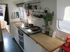 An issue with many small boats is the size of the kitchen and facilities you can incorporate. Through clever space saving design we have managed to include 3 large gas hobs (rather than the standard. Narrowboat Kitchen, Narrowboat Interiors, Tiny House Living, Small Living, Canal Boat Interior, Canal Barge, Narrow Kitchen, Nice Kitchen, Boat Storage