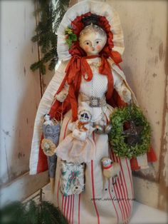 """By N. Sayre, The Gift giver is dressed in a cloak of antique white trimmed faded red cotton. Her skirt is antique ticking & her knitted warmer is  an antique doll bib  wrapped in a belt of velveteen picot ribbon & cut steel buckle.  She has a dresden cone with antique scrap & paper decoration & a tiny doll inside.  A china doll is bundled up in antique batting, a Putz sheep, early silver bells & an antique paper wreath with glittered star.   She is papier mache on her own stand 22"""""""