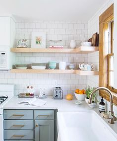 The light tones in this kitchen are beautiful! Rad white oak floating shelves!