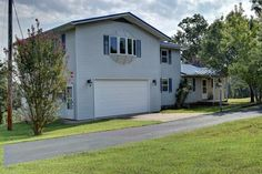 Beautiful lake view from this custom 4 bedroom 2 bath beauty overlooking Bull Shoals Lake on paved road. Gorgeous large trees cover this park like landscape in Peel AR