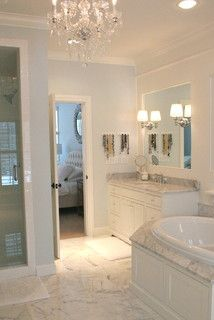 Master Bathroom: marble around tub with wood paneling on front
