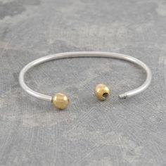Customisable Gold Torque Bangle - Versatile, uncomplicated and on-trend, this Customisable Gold Torque Bangle can be personalised by attaching sterling silver or eighteen carat rose or yellow gold plated balls to complete your desired look. #Otisjaxon #Jewellery