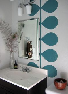 Modern Stem & Leaf Painted Bathroom Mural. Awesome way to add a pop of color with the rich teal blue against the gray walls. From Amy of Hey Now, Whoa Now via Remodelaholic.