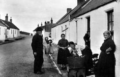Old photograph of fishwives washing day outside a cottage in Auchmithie, Angus, Scotland