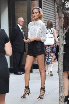 Celebrity Style at New York Fashion Week Spring 2016 - Chrissy Teigen in high waisted shorts, a prairie shirt, + chic lace up heels