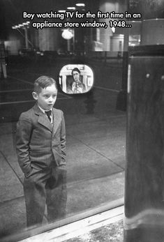 Boy watching TV for the first time in a store window, 1948.