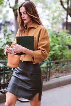 Leather skirt paired with a neutral button up blouse