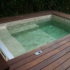 That is a drop-in unit with an automatic spa cover built into an Ipe deck: Bradford Products hot tub.