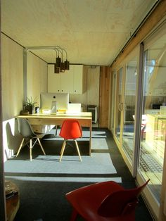 Shipping container office interior. Plywood clad walls and desks, industrial pendant lights, Eames molded plastic dowel leg chairs.  Connell Hull Company HQ!! Designed and built by Ben Hull.
