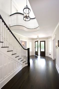 Railing Idea Grand formal foyer with dark hardwood floors and double front doors. Sweeping paneled staircase with white spindles and dark handrail. Curved balcony overlooking stairs, white walls and large glass and iron pendant. Style At Home, Future House, Exterior Design, Interior And Exterior, Door Design, Interior Balcony, Divider Design, Hall Interior, Floor Stain Colors