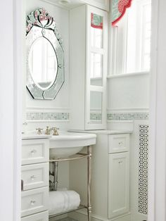 For a small bath, this room has plenty of storage and exceptional lighting. Built-in shelves make a huge difference, as they are both practical and aesthetically pleasing. Basin legs keep the room from looking too busy, while the natural light and white walls brighten the entire space.