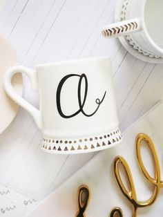 Our white ceramic mugs feature a monogram initial with gold spots and triangles around their base and inside the rims. With a fabulous chevron print along the handle, our mugs dishwasher and microwave safe.