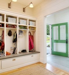 small mud room with cubbies, cool lighting and rugs as you come in the back door patio (love the green door!)