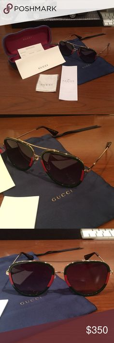 """GUCCI SUNGLASSES -Gold metal with green and red Web frame -Gold metal temples with black tips -Green shaded lens -100% UVA/UVB protection -GG0062S -Frame height 2"""" -Frame width 5.5"""" -Made in Italy -Glasses arrive in a velvet hard case, available in a range of six jewel-toned colors and paired with a coordinating satin lining. The case color selection will be individually selected for each pair of glasses and comes with a matching satin flannel pouch and ivory microfiber cloth.  Open to…"""