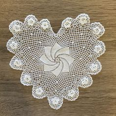 """Set the mood with this romantic heart shape doily. Hand crochet lace with plum rose around the edge. 100% cotton. 6"""" heart. Color: White. Available also in 4"""" R"""
