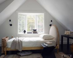 With a Light Touch  In the attic guest room, the bed is dressed with Sferra linens; the table is a Milo Baughman design, the sconces are by Vaughan Designs, and the rug is Turkish.