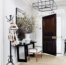 I love the graphic details... mixed metals, oversized floral arrangement and wire rimmed ceiling fixture. A cool entry.